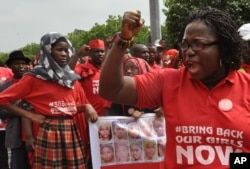 FILE - People take part in a march that is part of the 'Bring Back Our Girls' campaign, in memory of the Nigerian girls abducted by Nigerian extremists, outside the presidential residence in Abuja, Nigeria, July 8, 2015.