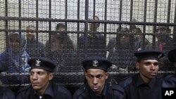 Policiers assis devant une cage abritant des employés égyptiens de plusieurs ONG pro-démocratie durant leur procès au Caire (26 fév. 2012)