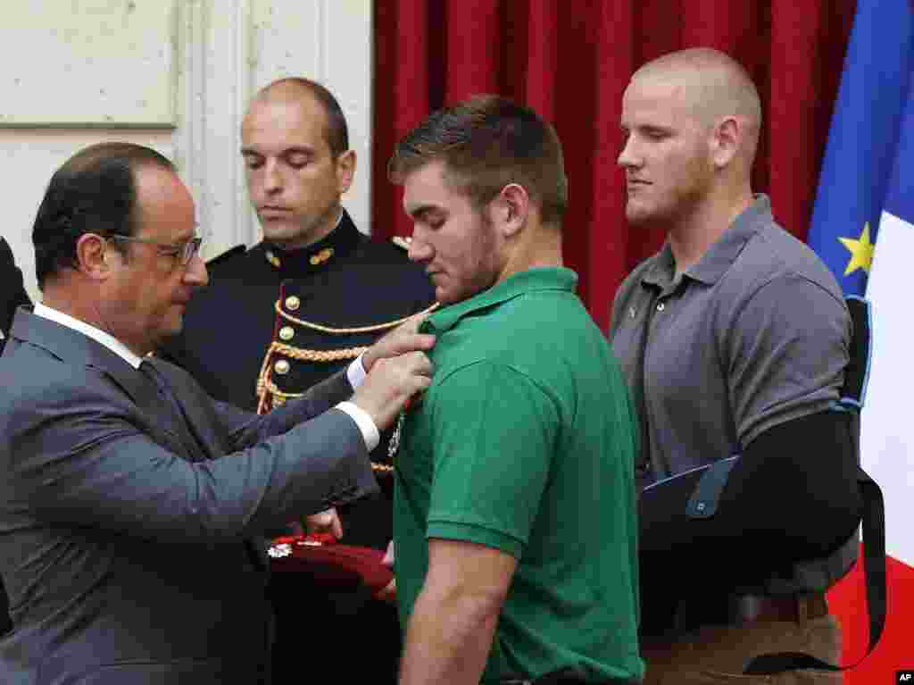 French President Francois Hollande bestows the Legion of Honor upon Alek Skarlatos, a U.S. National Guardsman from Roseburg, Oregon, while U.S. Airman Spencer Stone looks on at the Elysee Palace,  in Paris, Aug. 24, 2015.