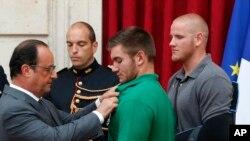 法国总统奥朗德把法国荣誉军团勋章别在美国国民警卫队成员阿列克·斯卡拉托斯身上,美国空军士兵斯宾塞·斯通在旁观看。(2015年8月24日)