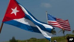 FILE - U.S. and Cuban flags fly. The countries re-established diplomatic relations earlier this year following a half century of estrangement.