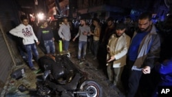 People gather near the site of a twin suicide attack in Burj al-Barajneh, southern Beirut, Lebanon, Thursday, Nov. 12, 2015 that struck a Shiite suburb.
