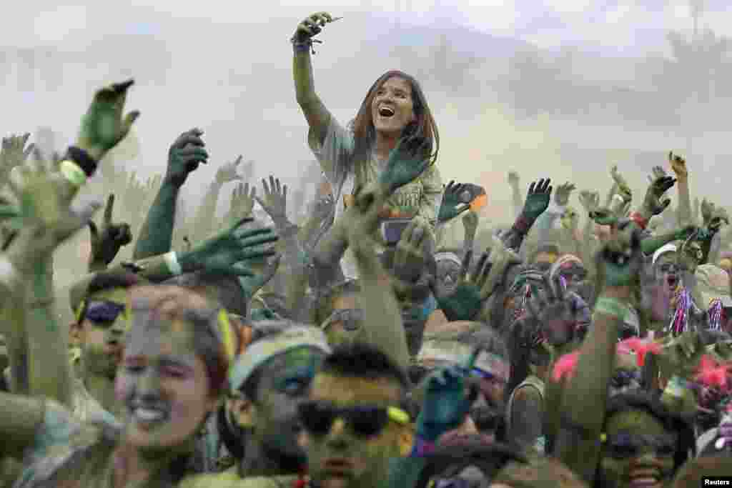 Participants cheer as they take part in The Color Run in Cali, Colombia, Nov. 3, 2013. The Color Run is a five-kilometer, untimed race, held in cities worldwide, with the aim of promoting healthy living. Participants are doused from head to toe in different colors at each kilometer.
