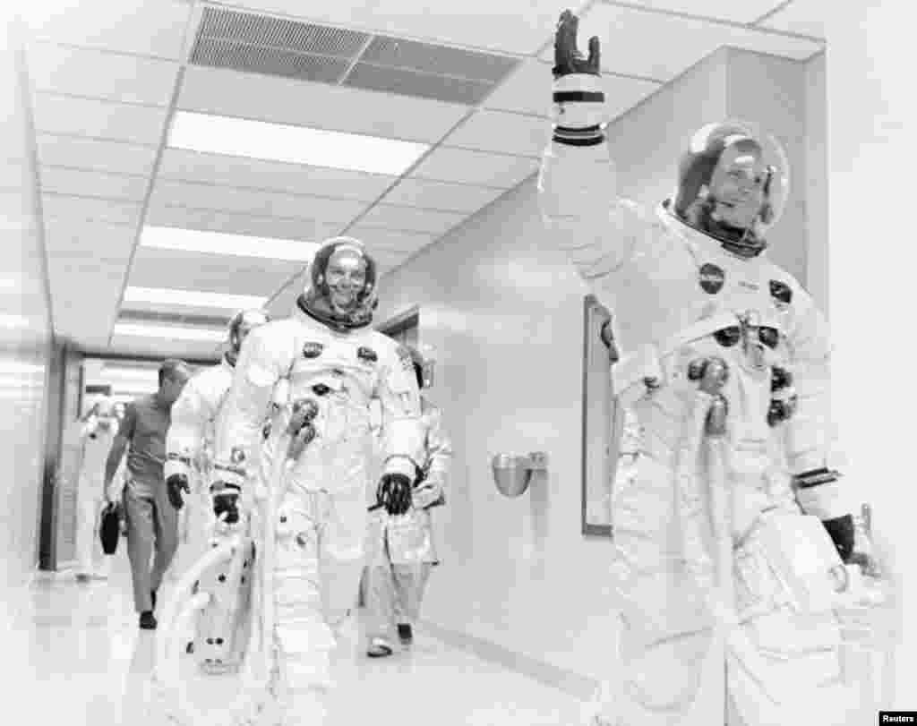 На этом фото астронавты, уже облаченные в скафандры, направляются к ракете «Сатурн-5». За несколько дней до исторического запуска Армстронг, Олдрин и Коллинз были помещены в предполетный карантин. Основанием для такого решения послужила миссия «Аполлон-9», которую пришлось отложить на несколько дней из-за недомогания астронавтов. Доступ к участникам «Аполлона-11» был строго ограничен: лишь узкий круг специалистов НАСА, а также члены семей астронавтов (не имевшие к тому же симптомов заболеваний) могли с ними контактировать. Во время пресс-конференции перед полетом астронавты находились в специальной пластиковой будке в 15 метрах от журналистов. Нарушить карантин не позволили даже президенту США: Ричард Никсон пригласил их на обед за день до запуска, однако глава Белого дома был вынужден ограничиться лишь телеграммой и телефонным звонком.