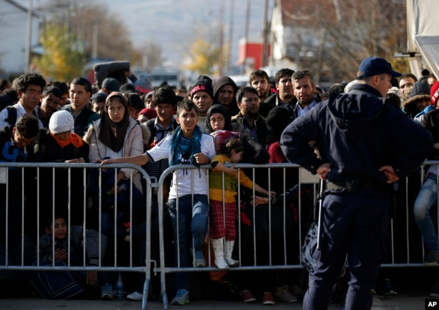 FILE - Migrants wait to register with police at a refugee center in the southern Serbian town of Presevo, Nov. 16, 2015.