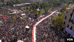 Gambar yang dirilis dari SANA (Syrian Arab News Agency) menunjukkan ratusan pendukung presiden Bashar al-Assad di Aleppo, Suriah (19/10).