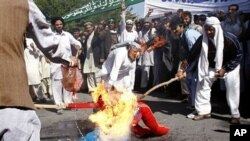 Afghan protesters burn an effigy of U.S. President Barack Obama during a demonstration in Jalalabad, Afghanistan on Sunday, April 3, 2011