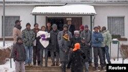 庇護申請者站在德國柏林西南大約135公里的拜德貝爾茲貝格的一處難民收容中心外。 (資料照)