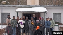 FILE - Asylum seekers stand outside an accommodation at a refugee holding center in the town of Bad Belzig some 135 km (84 miles) southwest of Berlin.