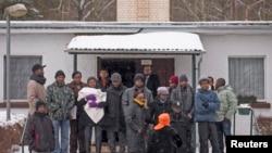 庇护申请者站在德国柏林西南大约135公里的拜德贝尔兹贝格的一处难民收容中心外。(资料照)