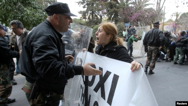 A protester tries to pass a police cordon during a rally by bank employees in Nicosia, Mar. 21, 2013.