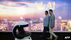 在北京中国国际展览中心举办的第十四届中国国际公共安全与安防博览会上,参观者从一台名为APV3的AI(人工智能)安防机器人身边走过,该机器人配备了人脸识别系统。