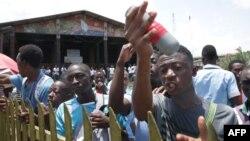 Des étudiants montrent une cartouche de gaz lacrymogène lancée par la police anti-émeute lors de leur rassemblement pour protester contre une modification des règles régissant le processus d'attribution de subventions, le 10 avril 2019 à Libreville.