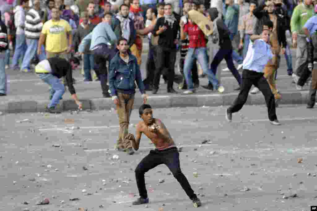 Protesters hurl stones during clashes between supporters and opponents of President Mohamed Morsi in Alexandria, Egypt, November 23, 2012.