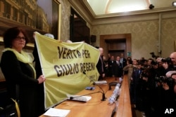 Paola, the mother of Giulio Regeni, holds a banner reading: Truth for Giulio Regeni, prior to the start of a press conference held at the Italian Senate, in Rome, Tuesday, March 29, 2016.