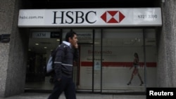 FILE - A man walks past a HSBC branch in Mexico City.