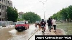 Les piétons marchent sur un trottoir boueux tandis que les véhicules pataugent dans une rue inondée par des pluies diluviennes à N'Djamena, au Tchad, le 19 août 2020. (Photo: André Kodmadjingar/VOA)