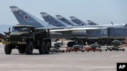 FILE - In this June 18, 2016, photo, Russian fighter jets and bombers are parked at Hemeimeem air base in Syria.