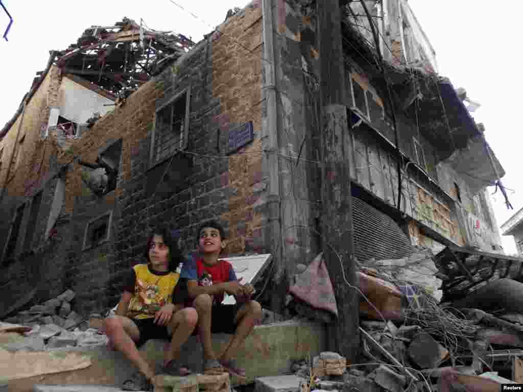 2013年9月19日,在被围攻的霍姆斯地区,儿童坐在一条遭到战争重创的街道旁。