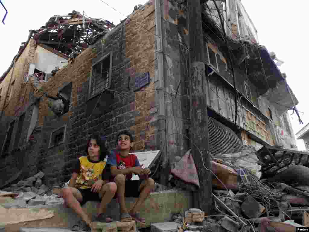Children sit along a damaged street filled with debris in the besieged area of Homs, Sept. 19, 2013.