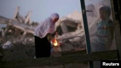 一名巴勒斯坦婦女在臨時避難所外煮咖啡, 她的居所被以色列砲擊摧毀