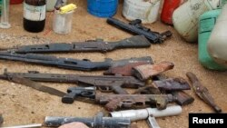 FILE - Confiscated weapons are displayed after a military raid on a hideout of suspected Islamist Boko Haram members in Nigeria's northern city of Kano, Aug. 11, 2012.