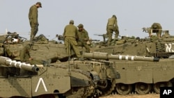 Israeli soldiers work on their a tanks in a staging ground in southern Israel, near the border with Gaza Strip, November 17, 2012.