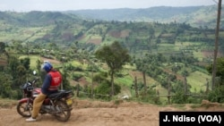 Motorcycle rider is seen with Kenya's Mau Forest village in the background.