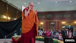 His Holiness the Dalai Lama waving to the audience