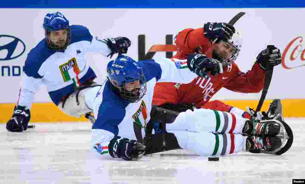 Andrea Macri of Italy and Morten Vaernes of Norway fight for the puck during the Ice Hockey Group A Preliminary Game between Norway and Italy at the Gangneung Hockey Centre at the Paralympic Winter Games, PyeongChang, South Korea, March 19, 2018.