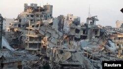 A general view shows damaged buildings on a deserted street in the besieged area of Homs Jul. 13, 2013.