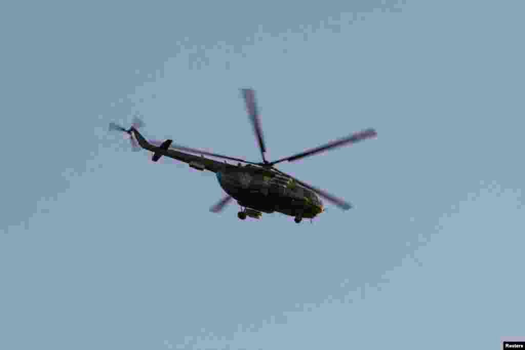 A Russian military helicopter flies near Simferopol, March 3, 2014.