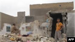 Cư dân tìm kiếm tư trang trong các đống đất đá đổ nát sau vụ nổ bom tại một khu vực ở hướng nam Baghdad