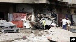 人们2012年6月13日检查易伊拉克巴格达周边发生的一起汽车炸弹爆炸攻击事件的现场
