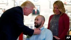 El presidente Donald Trump, otorga un Corazón Púrpura al sargento del Ejército de Estados Unidos de Primera Clase, Álvaro Barrientos junto a su esposa Tammy Barrientos, en el Centro Médico Militar Nacional Walter Reed, el sábado 22 de abril de 2017, en Bethesda, Md.