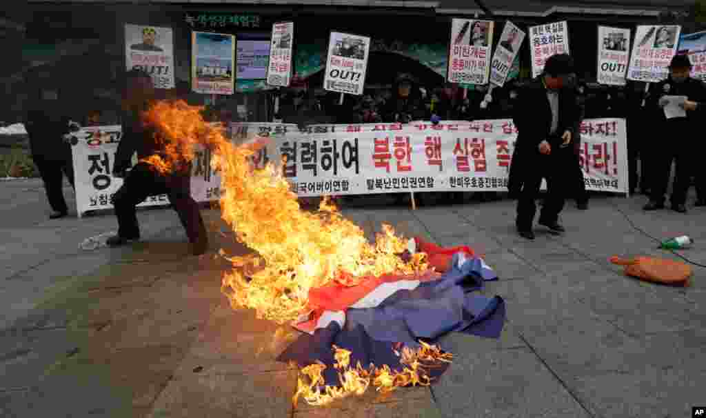 South Korean protesters burn a North Korean flag following a report of the nuclear test conducted by North Korea, in Seoul, South Korea, February 12, 2013.