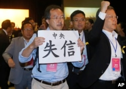 "FILE - Pro-democracy lawmaker Fernando Cheung holds a placard which reads "" Central Government break the promise "" as he protests against Li Fei, deputy secretary general of the National People's Congress Standing Committee, during a briefing session in Hong Kong."