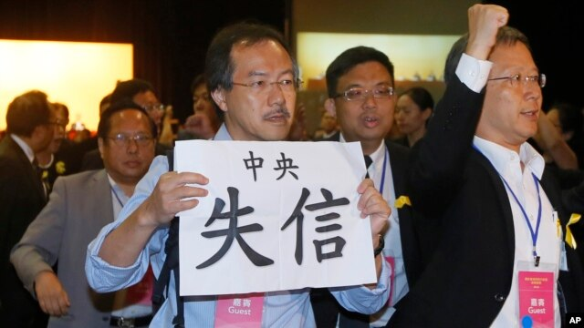 "FILE - Pro-democracy lawmaker Fernando Cheung holds a placard which reads "" Central Government break the promise "" as he protests against the deputy secretary general of the National People's Congress Standing Committee, during a session in Hong Kong, Sept. 1, 2014."