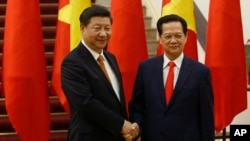 FILE - Chinese President Xi Jinping, left, poses for a photo with Vietnam's Prime Minister Nguyen Tan Dung before their meeting in Hanoi, Nov. 5, 2015.
