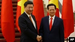 Chinese President Xi Jinping, left, poses for a photo with Vietnam's Prime Minister Nguyen Tan Dung before their meeting at the Government Office, Hanoi, Nov. 5, 2015.