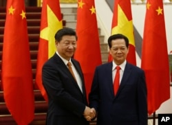 FILE - Chinese President Xi Jinping, left, poses for a photo with Vietnam's Prime Minister Nguyen Tan Dung before their meeting at the Government Office in Hanoi, Nov. 5, 2015.