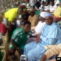 Dan wasan Najeriya, Obafemi Martins, yana gaida Muhammadu Buhari, a filin wasa na kasa dake Abuja lokacin wasan Najeriya da Ethiopia, Lahadi 27 Maris 2011