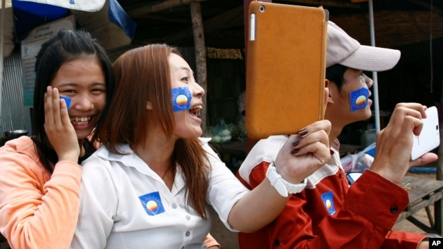 A supporter, center, of the newly merged Cambodia National Rescue Party, holds an iPad during an election campaign on the outskirts of Phnom Penh, Jul. 3, 2013.