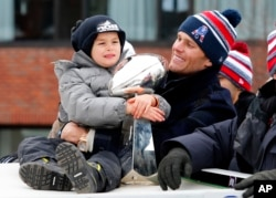 Patriots quarterback Tom Brady looks on as his son, Benjamin, hugs the Vince Lombardi Trophy, given to the Super Bowl champs each year, during the team's parade in Boston, Feb. 4, 2015.