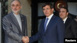 Iranian Foreign Minister Ali Akbar Salehi (L) and his Turkish counterpart Ahmet Davutoglu are seen before a meeting in Ankara, Turkey, August 7, 2012.