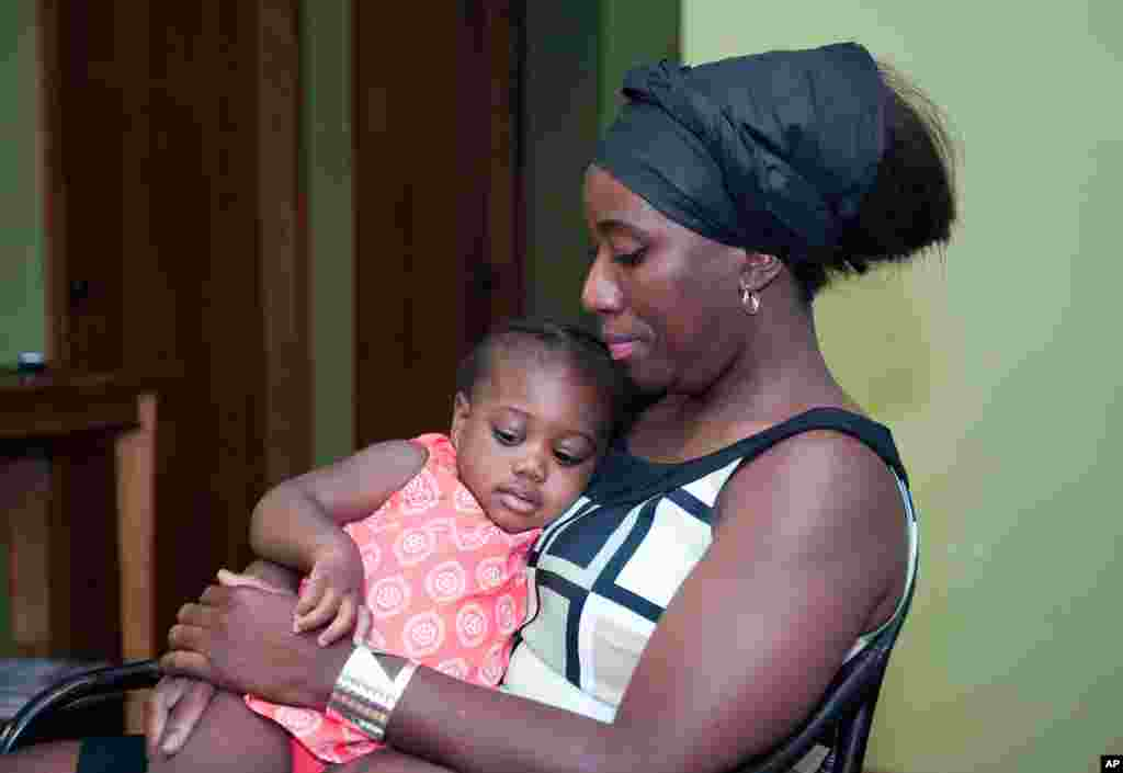 Decontee Sawyer, wife of Liberian government official Patrick Sawyer, a U.S. citizen who died from Ebola after traveling from Liberia to Nigeria, cradles her 1-year-old daughter, Bella, at her home in Coon Rapids, Minnesota, July 29, 2014.
