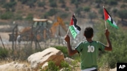 A Palestinian boy holds Palestinian flags as an Israeli tractor removes parts of a section of Israel's separation barrier between the outskirts of the West Bank village of Bilin, near Ramallah, and the Jewish settlement of Modiin Illit, Sunday, June 26, 2
