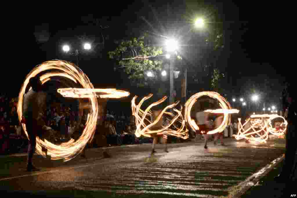 "Fire-dancers perform during the ""Esala Perahera"" festival near the Buddhist temple of the Tooth in the ancient hill capital of Kandy, some 116 kilometers from Colombo, Sri Lanka, Aug. 14, 2019."