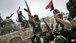 Libyan rebel fighters shoot in the air and shout religious slogans as they attend the funeral of 7 fallen comrades killed the day before during the battle for the control of the oil rich town of Brega at the main cemetery in the Libyan rebels stronghold c