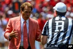 Alabama football coach Nick Saban talks with a referee during the first half of an NCAA spring game, April 21, 2018, in Tuscaloosa, Alabama. The Crimson Tide are the defending national champions.